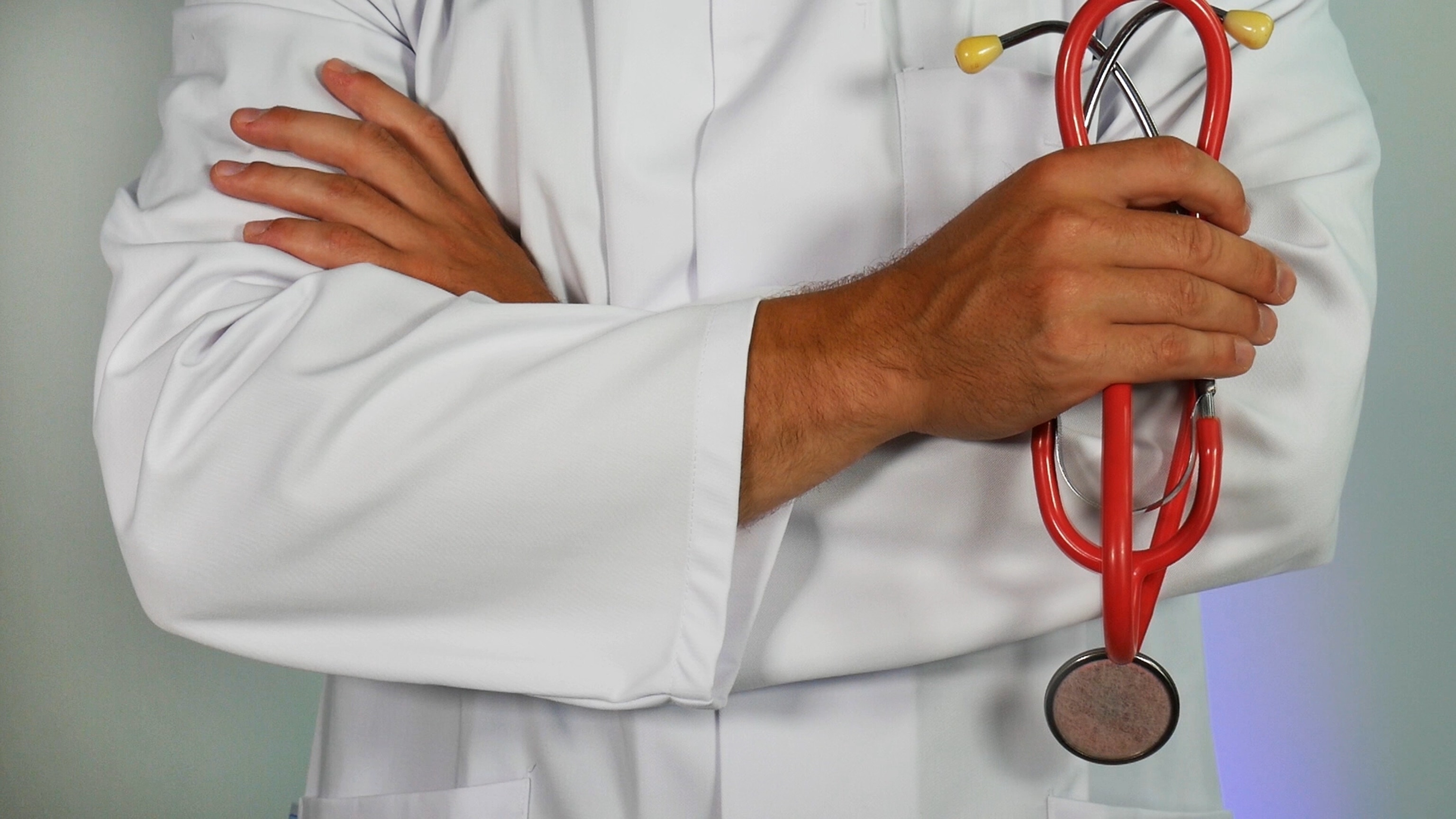 A person in medical attire with a red stethoscope in hand